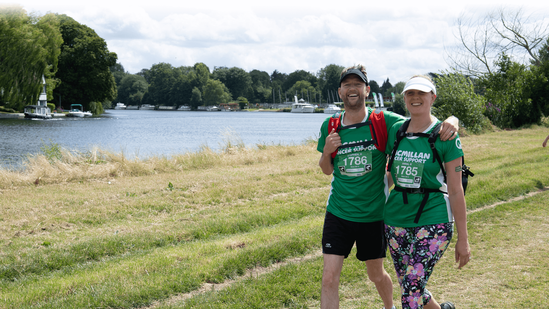 A man and a woman walking along a grassy section of the Thames path next to the Thames