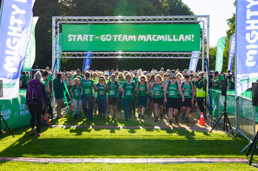 A large group of people in green tops standing at the start line of a walk