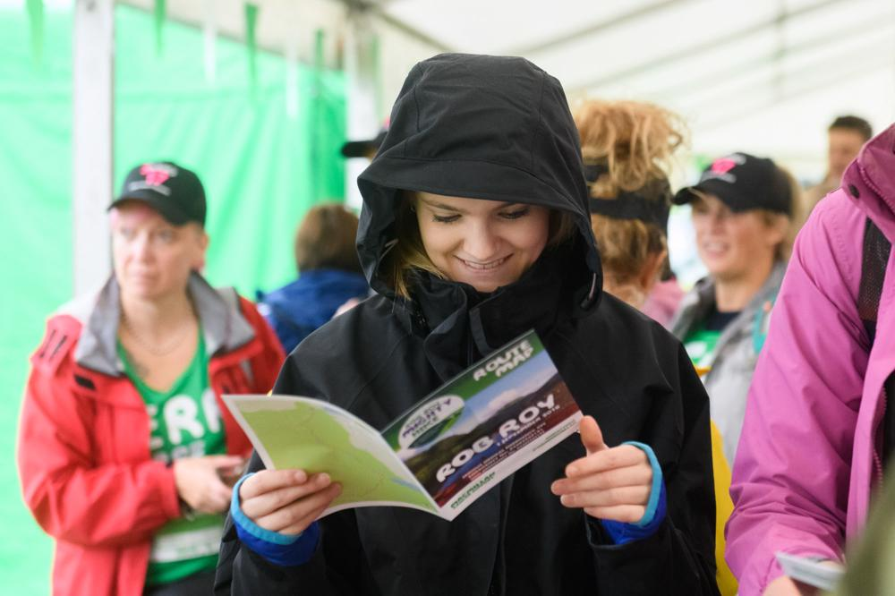 A woman in a black waterproof jacket reading a leaflet about the Rob Roy Mighty Hike