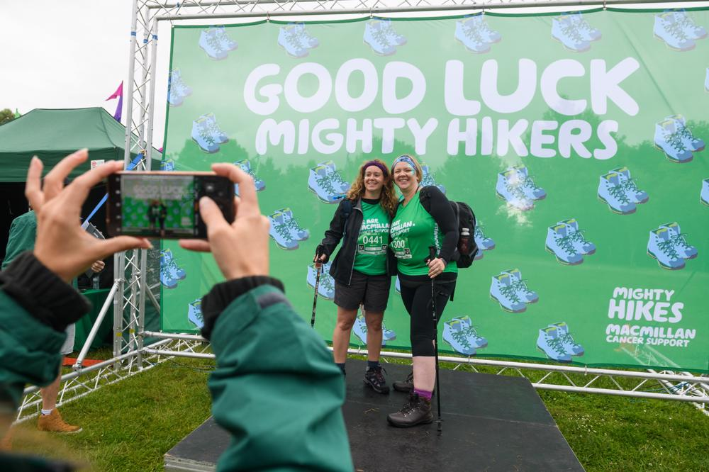 Two women posing for a photo against a 'Good Luck Mighty Hikers' backdrop