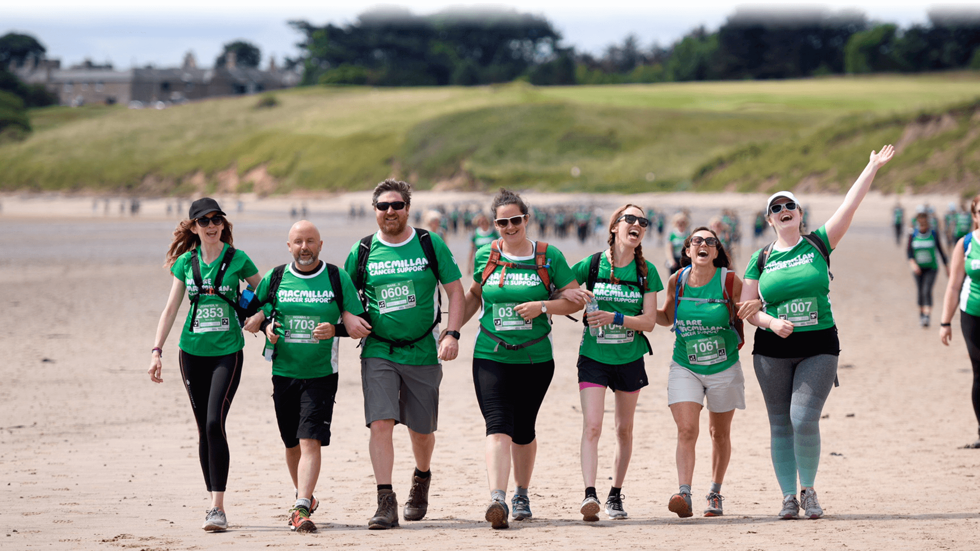 Seven hikers in green, walking along a beach with their arms linked together