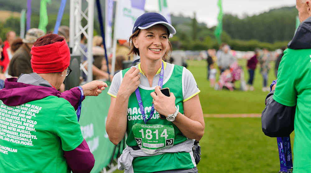 A woman in a green vest and cap holding a finishers medal around her neck and smiling
